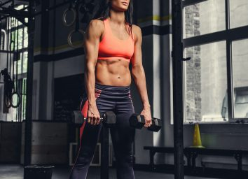 Brunette fitness woman doing biceps workouts with dumbbells in a gym.