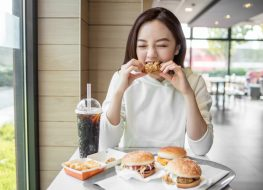 young woman eating chicken in fast food restaurant