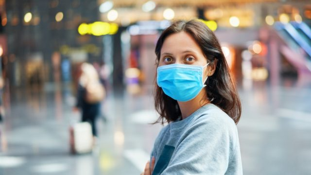 Traveler woman in virus protection face mask in international airport.