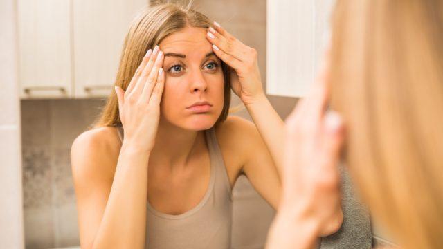 Worried woman is looking her wrinkles in the bathroom.