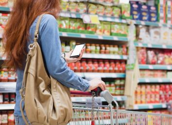 young woman with red hair holding a tan purse and cell phone and pushing a cart while grocery shopping