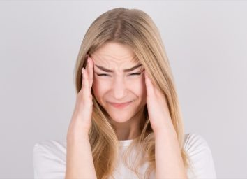 Young woman with a headache holds her temples with her hands.