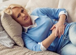 Mature woman in casual clothes is having a stomach ache while lying on couch at home.