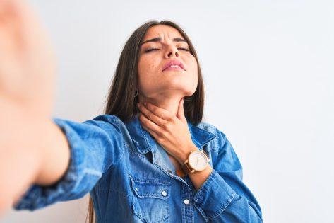 Woman touching painful neck.