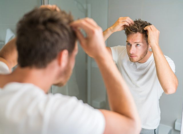 young man in white t-shirt and jeans looking in mirror at thinning hair