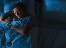young blond man sleeping in bed at night