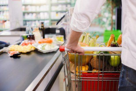 man in white shirt pushing cart through grocery store checkout lane