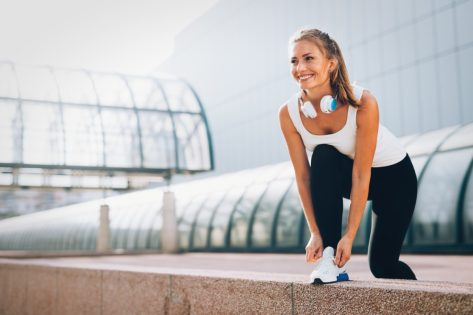 happy young woman lacing her sneakers outdoors