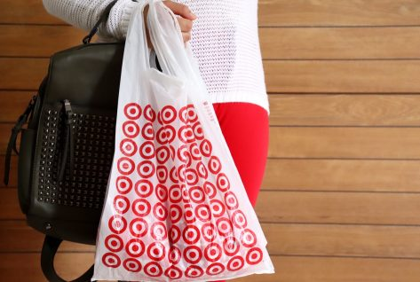 stylish young woman in white top and red pants holding black purse and target bag against wooden background