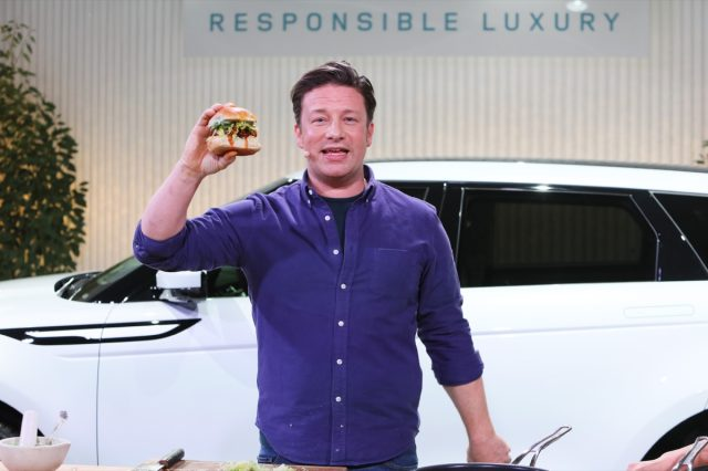 jamie oliver in blue shirt standing in front of a white car holding up a burger in one hand
