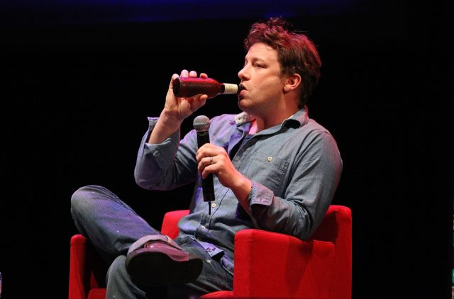 jamie oliver in a chambray shirt and jeans drinking a beer