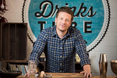 """jamie oliver in blue plaid shirt standing in front of blue circular wooden sign reading """"drinks"""""""