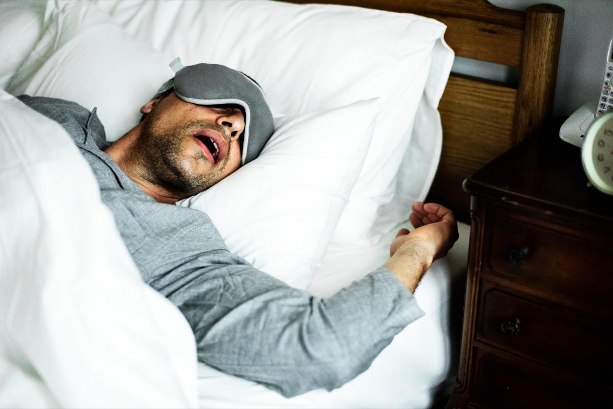 pria paruh baya dengan kemeja abu-abu dan topeng tidur tidur dengan mulut terbuka