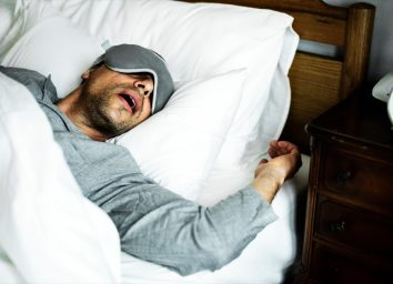 middle aged man in gray shirt and sleep mask sleeping with mouth open