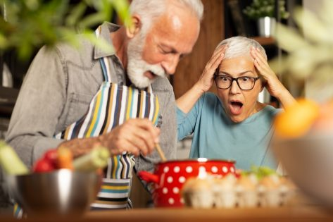 Senior woman shocked, with open mouth looking at her husband cooking.