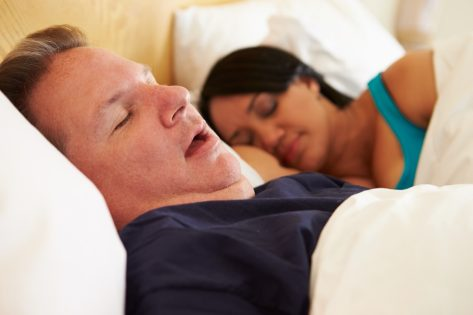 middle aged man and woman sleeping in bed