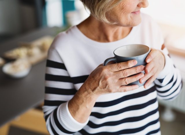 older woman in striped top drinking coffee