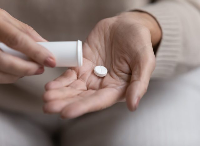 older woman taking pill or supplement
