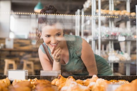 woman looking into pastry case
