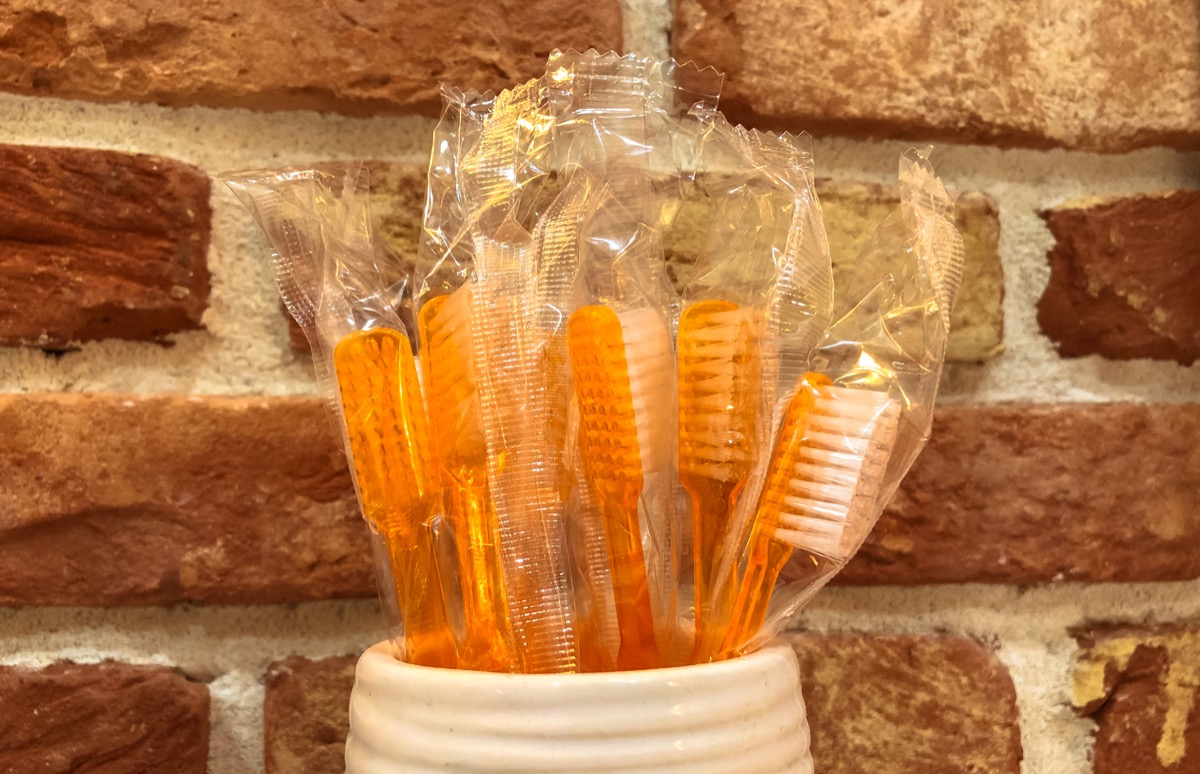 a bunch of orange toothbrushes wrapped in plastic