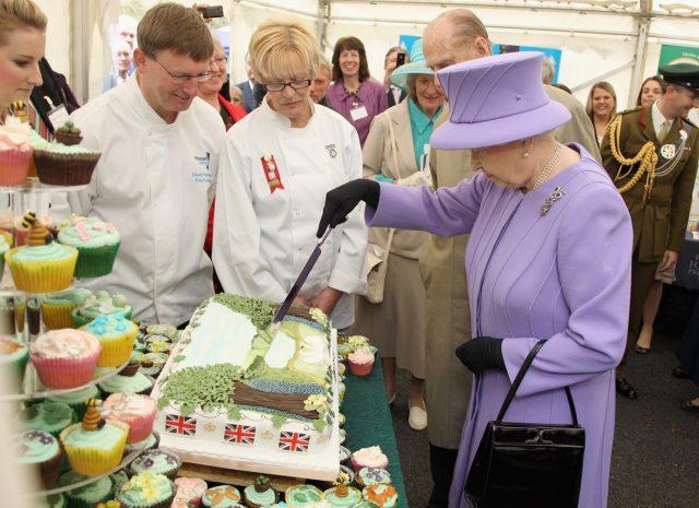 queen elizabeth in a purple suit cutting cake