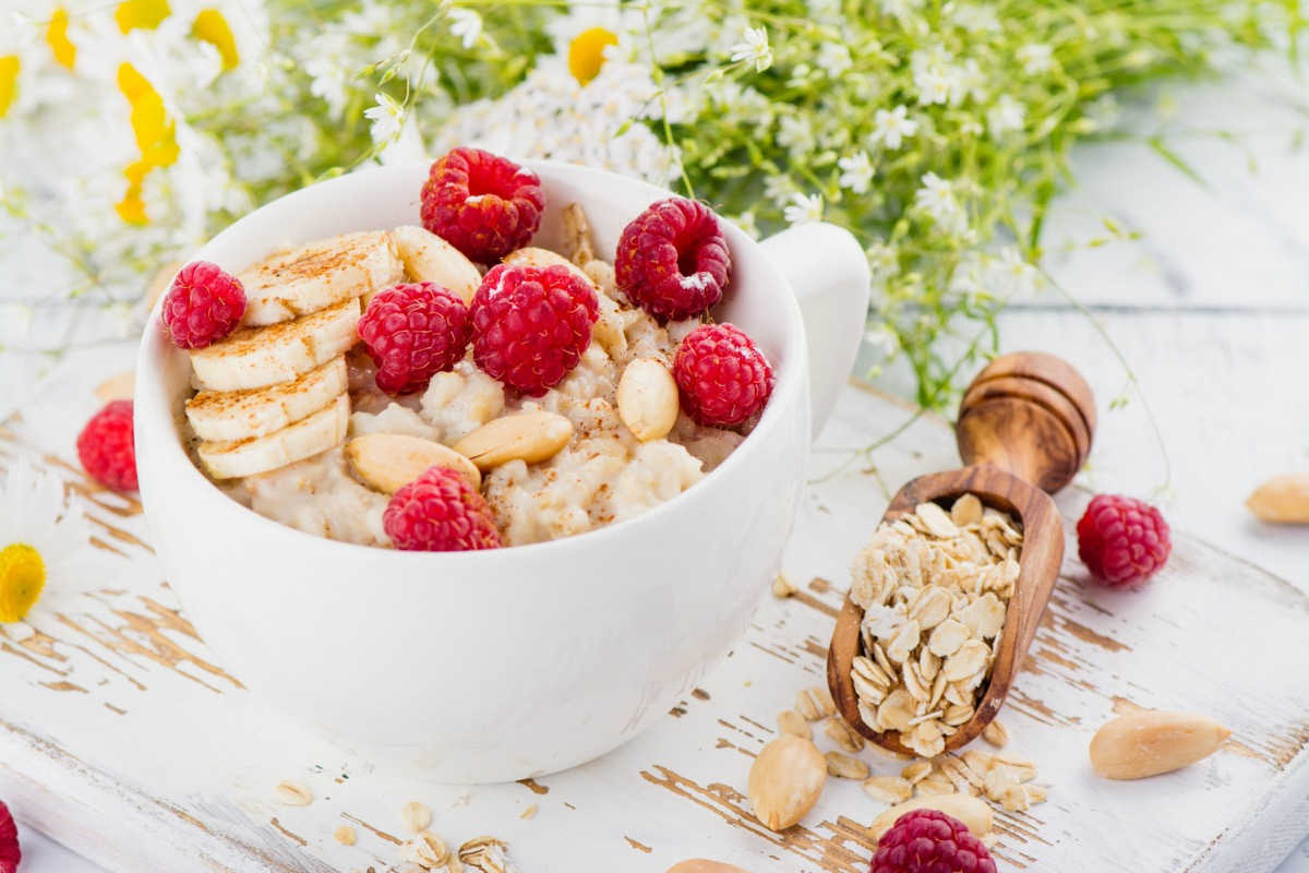 oatmeal topped with raspberries and bananas in a white bowl