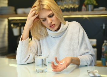 Woman holding pills in her hands.