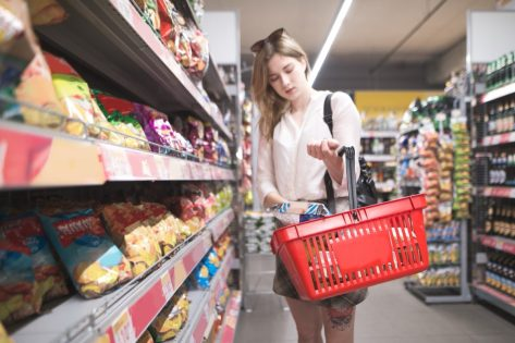 young woman shopping snack aisle in supermarket