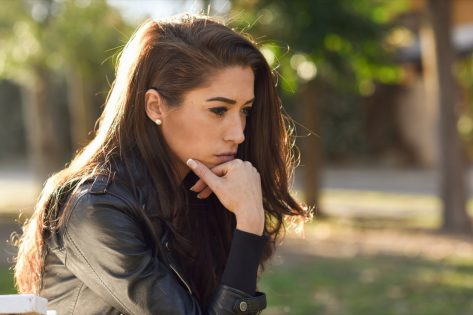 young woman looking stressed and sitting outdoors
