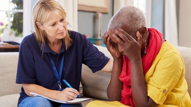 middle aged woman with memory loss or alzheimer's or dementia talking to doctor or nurse at home