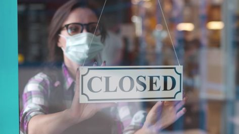woman putting closed sign into restaurant window