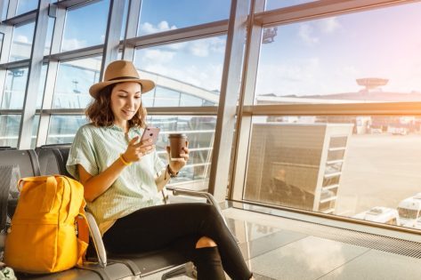 young woman in fedora drinking coffee at airport