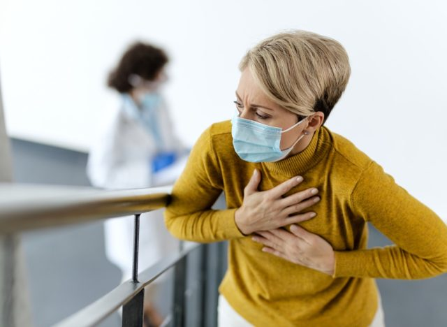 Sick woman feeling chest pain and wearing face mask in a lobby at medical clinic.