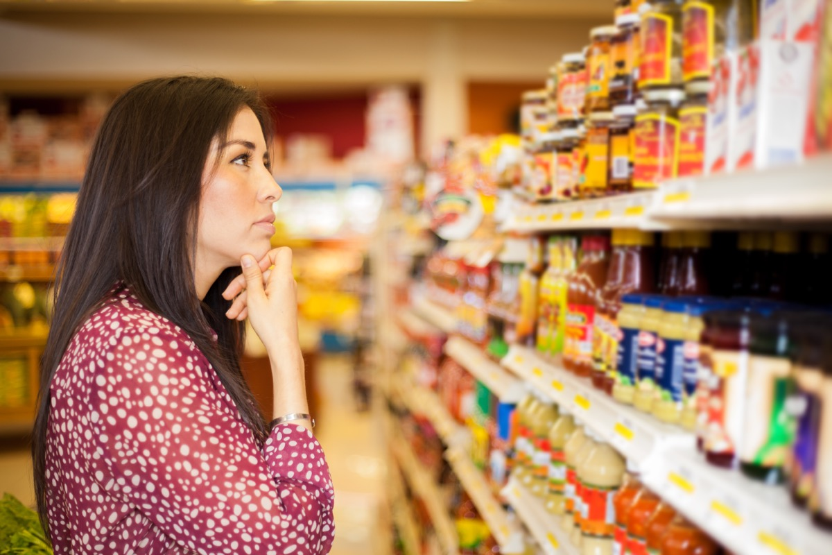 young woman looking at shelf of sauces appearing confused at grocery store