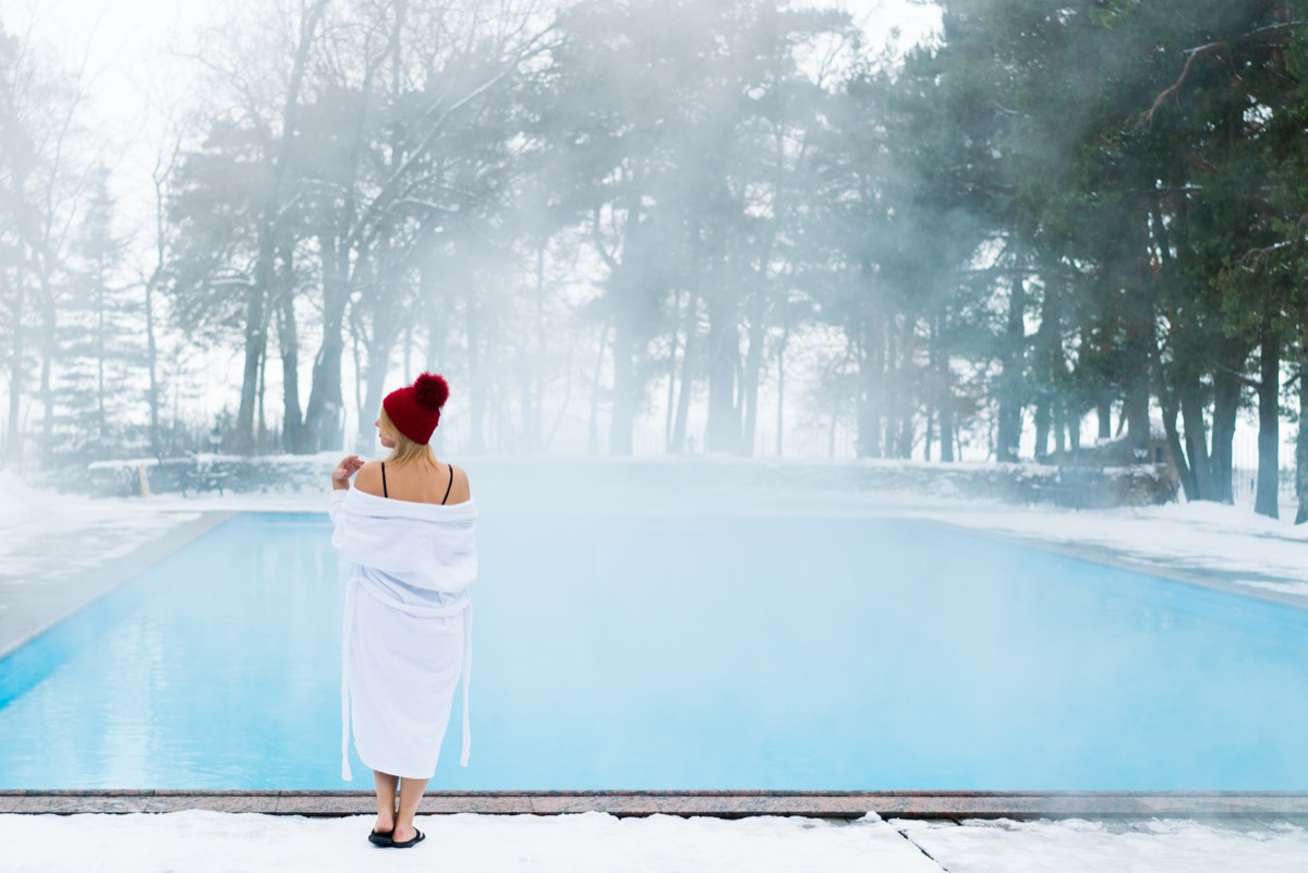 woman in robe getting into pool on cold day in winter