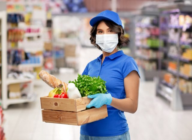 Delivery woman in face protective medical mask and gloves holding wooden box with food in supermarke.