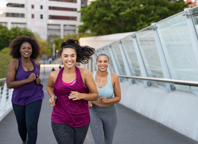 group of young, attractive multiracial women running in tank tops and leggings across a modern bridge