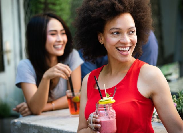 young woman outdoors in red shirt drinking smoothie while her friend behind her drinks iced tea