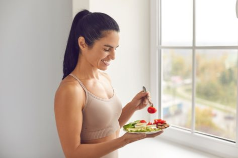 young woman in tan top and ponytail eating a healthy meal in front of a window