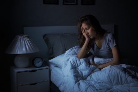 young woman holding face in bed in the dark dealing with insomnia or poor sleep