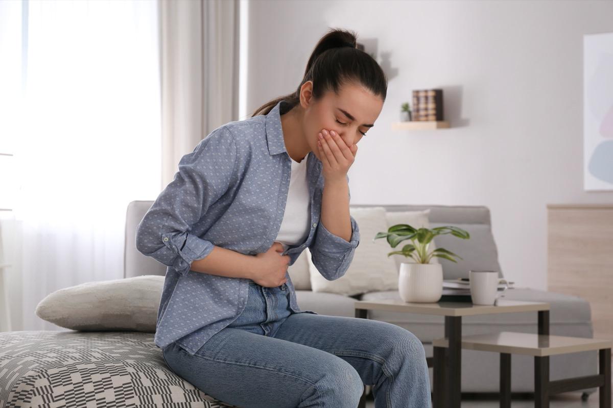 Mujer joven con náuseas en toda la ropa de mezclilla sentada en la cama
