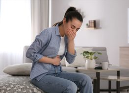 young woman with nausea in all denim outfit sitting on bed