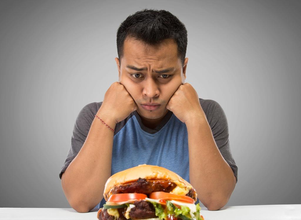 man staring at fast food burger