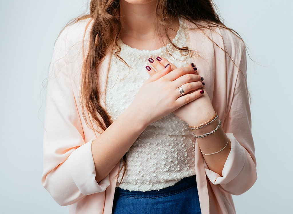 Young woman clutching chest