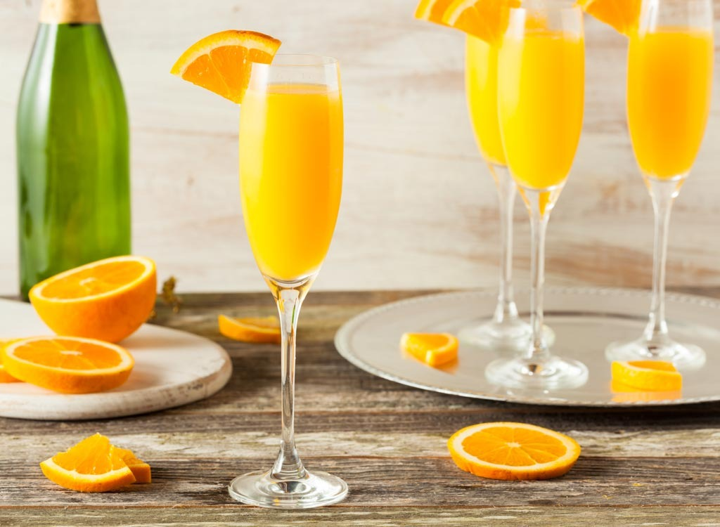 mimosa cocktails in glasses with orange slice on rim