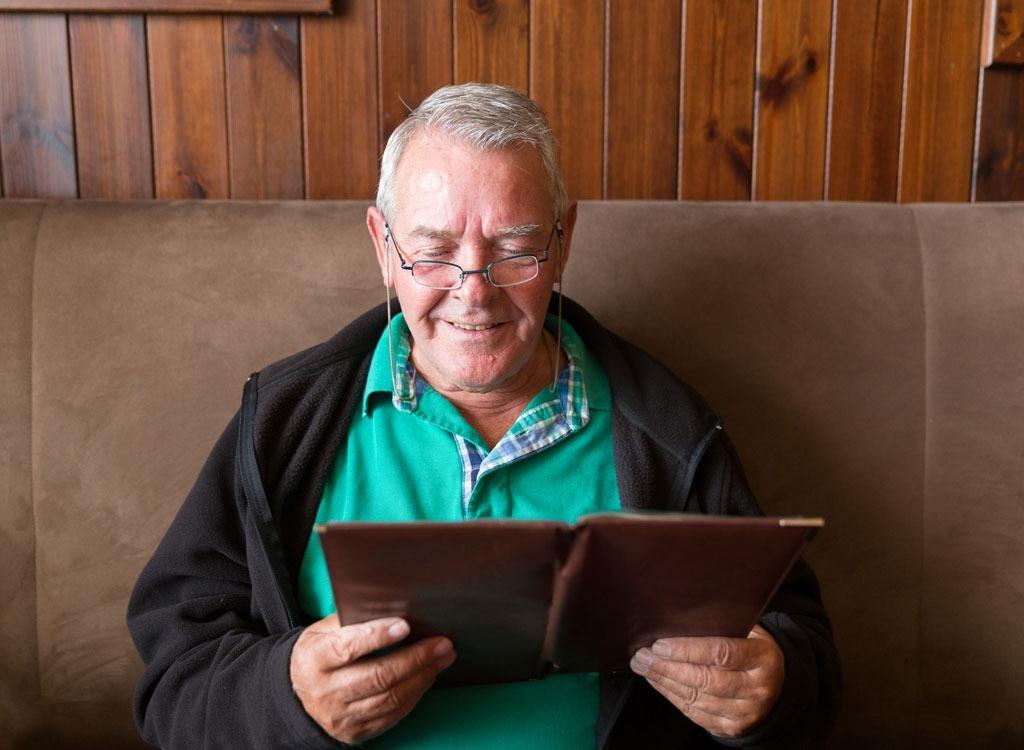 man smiling at menu