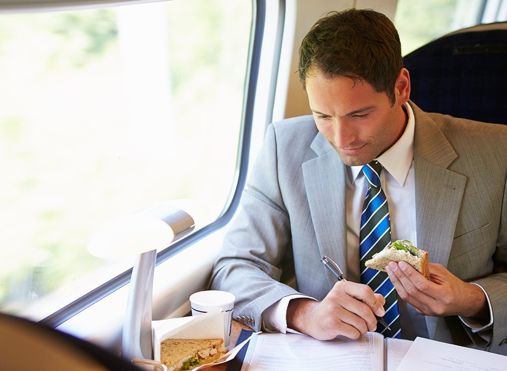 Man on train eating lunch and working