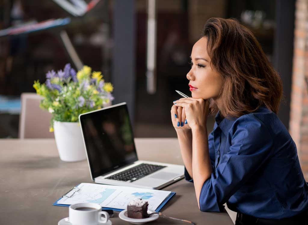 Woman at laptop thinking - stop thinking about food