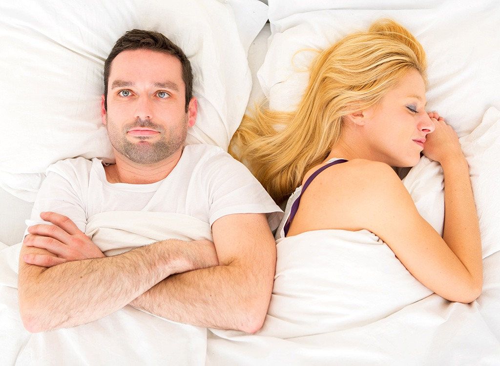 Man lying awake in bed next to woman - what happens when you dont drink enough water