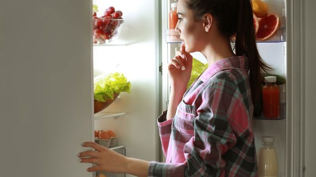 Woman looking in refrigerator late at night
